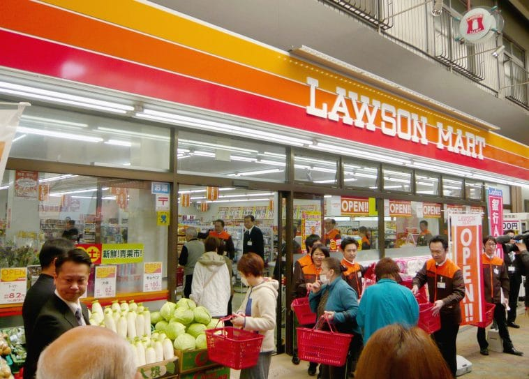 The entrance to the Lawson convenience store is crowded with the customers walking in and out