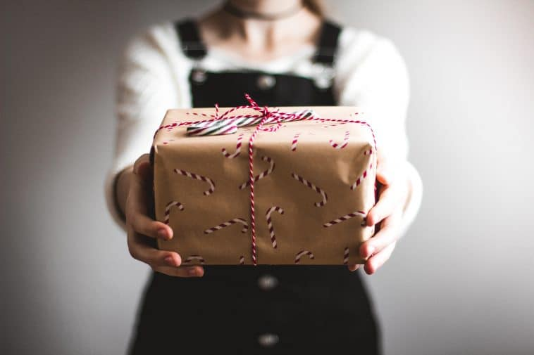 A woman is holding a gift box in front of her