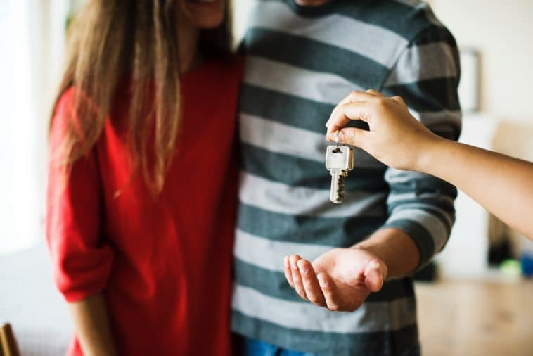 A person's hand is handling keys to a couple, a men stretches his arm to get the keys