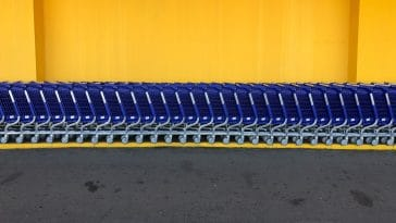 A line of blue shopping supermarket carts stand against the yellow wall